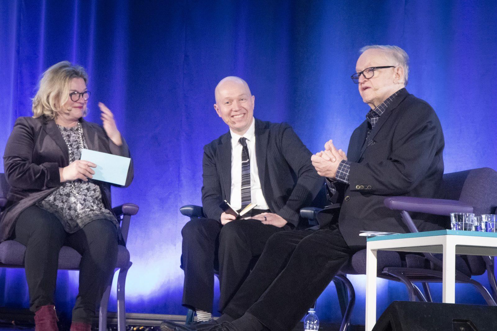 CMI:n viestintäjohtaja Elina Lehtinen haastattelemassa Marko Ahtisaarta ja presidentti Martti Ahtisaarta Aalto-yliopiston keskustelutilaisuudessa.